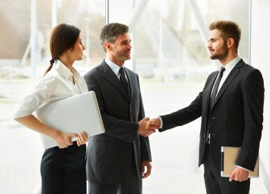 Two men shaking hands with woman standing next to them