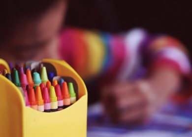 Pack of crayons with a child coloring in the background