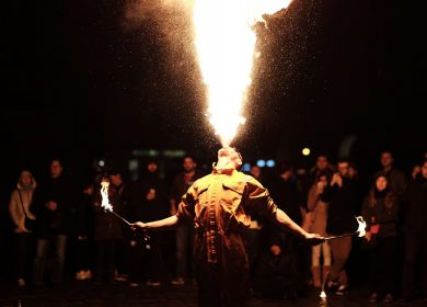 Man blowing fire up in the air from his mouth