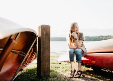 Woman sitting between two boats on grass near body of water
