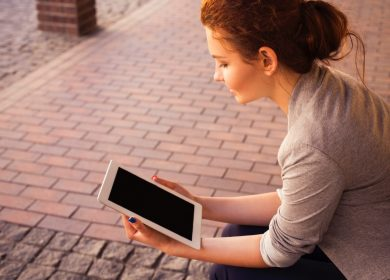 Woman holding a tablet with a brick floor background