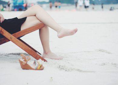 View of person on a lounge chair on the sand