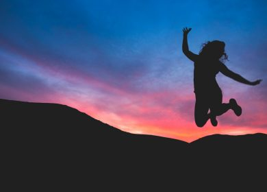 Woman shadow jumping in the air with sunset background