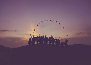 Group of people throwing up their graduation caps against a sunset