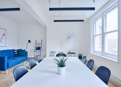 Long table with blue chairs tucked into it with a blue couch and large window in the background