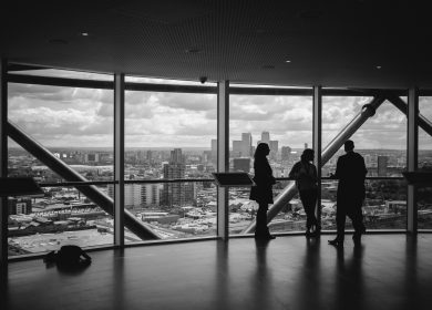 Black and white view of people in a room with large windows viewing a city in the background
