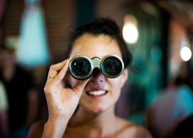 Woman looking into the camera with binoculars