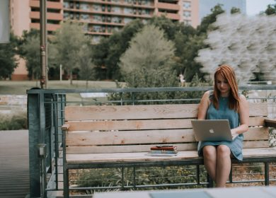Woman sitting on a wooden bench with a back with a laptop on her lap with buildings and trees in the background