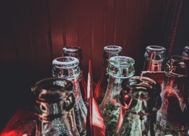 View of the tops of glass bottles on a red background