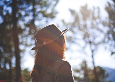 Woman with a hat looking at trees facing away from the camera