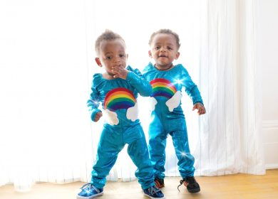 Two little boys in matching rainbow pajamas