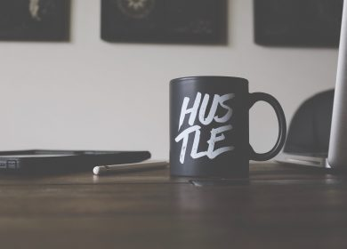Desk with Hustle coffee cup on it