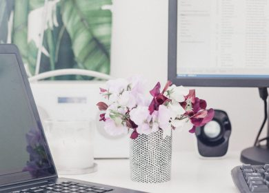 Vase with pink flowers on table with laptop to the left and computer screen to the right with window in the background with trees