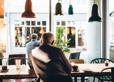 Man sitting in a cafe facing a window looking out