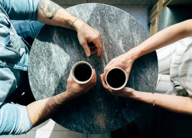 View from the top of two sets of hands at a table holding coffee cups
