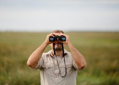 Man looking into binoculars facing camera with beige shirt on with a field in the background