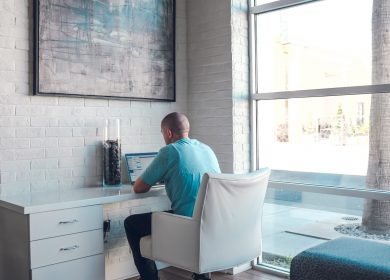 Back of man sitting at desk next to window