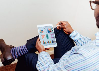 Image of man sitting with tablet looking at statistics