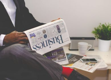 Man sitting with leg crossed holding a Business newspaper