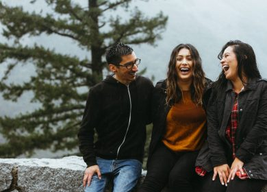 Man and two women sitting and laughing with a tree in the background