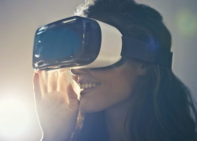 Woman looking to the left while wearing Virtual Realty mask on and holding them up with her right hand
