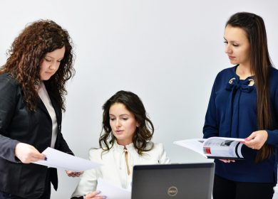 Two women standing next to a woman in front of a laptop