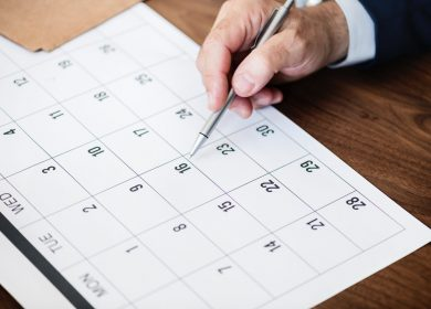 Calendar with Man's hand pointing to a date with a pen