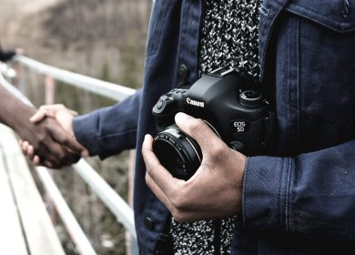 Two hands shaking with one person holding a camera close to belly