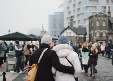 Two people walking away from camera with one holding the other by the waste down a street full of people
