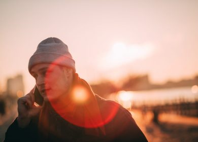 Man with a beanie with a phone to his ear with the sunrise in the background