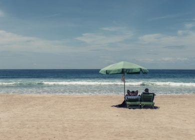 Two people in lounge chairs under an umbrella facing a beach with small breaking waves