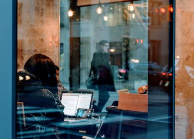 View of person with a parka on looking at laptop in a cafe