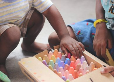 Two kids squatting down next to a container of colored chalk