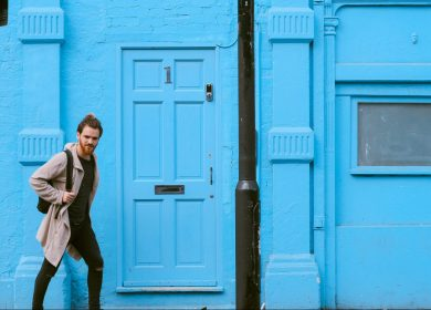 Man walking in front of a blue building with a blue door
