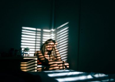 Woman in corner of room with shadow of blinds over her