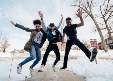 Three people jumping up in the air with their hands up in the air